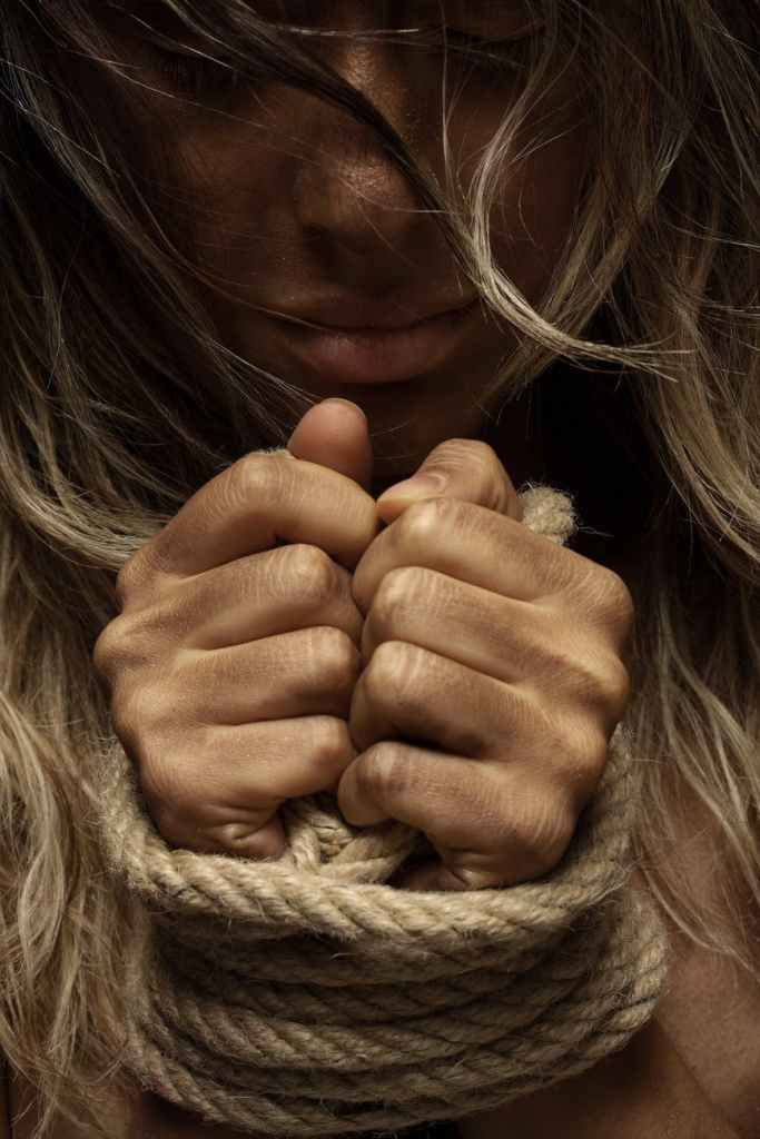woman whose hands are bound with rope